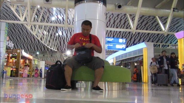 Duduk di sofa hijau Bandara Sultan Hasanuddin